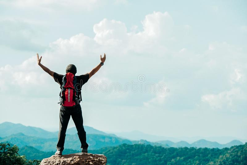 Hiker asian man happy feeling freedom good and strong weight victorious facing on the natural mountain. Travel Concept stock photo