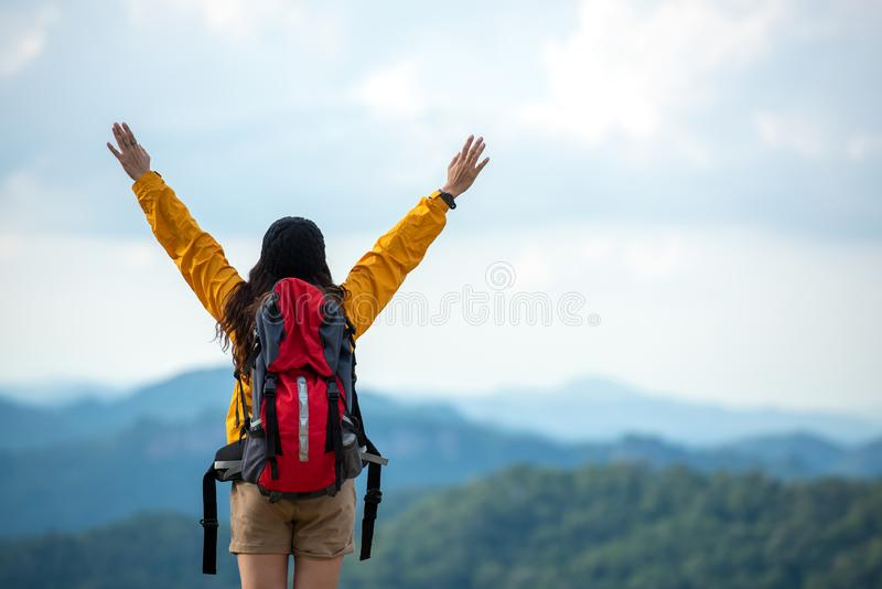 Hiker asian women raise hand and pointing happy feeling freedom good and strong weight victorious facing on the natural mountain. Traveler going camping stock image