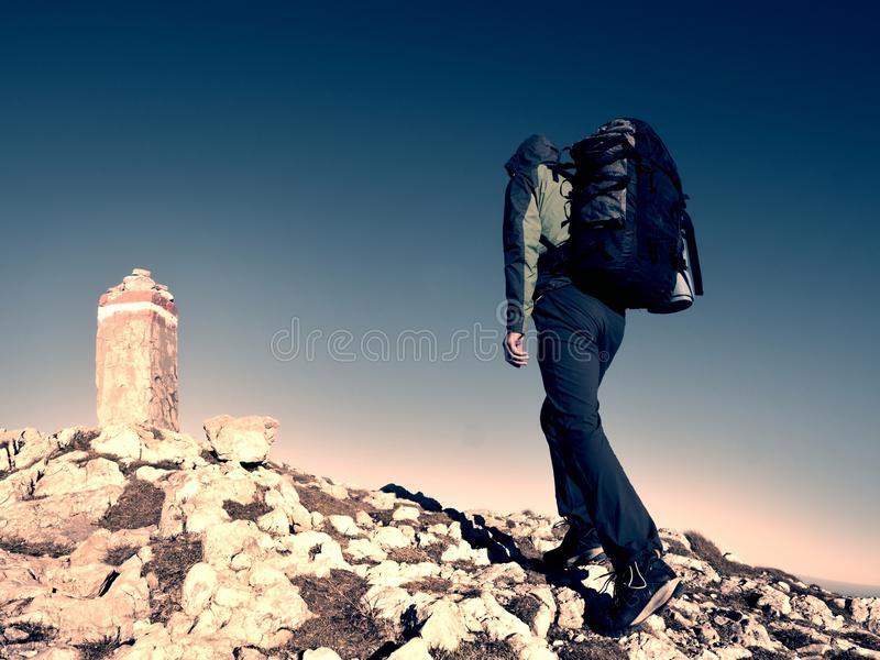 Hiker with backpack climbing on mountain peak. Summit stone in Alps. Hiker with backpack climbing on mountain peak. Summit stone at Alps mountain top. Tourist royalty free stock photography