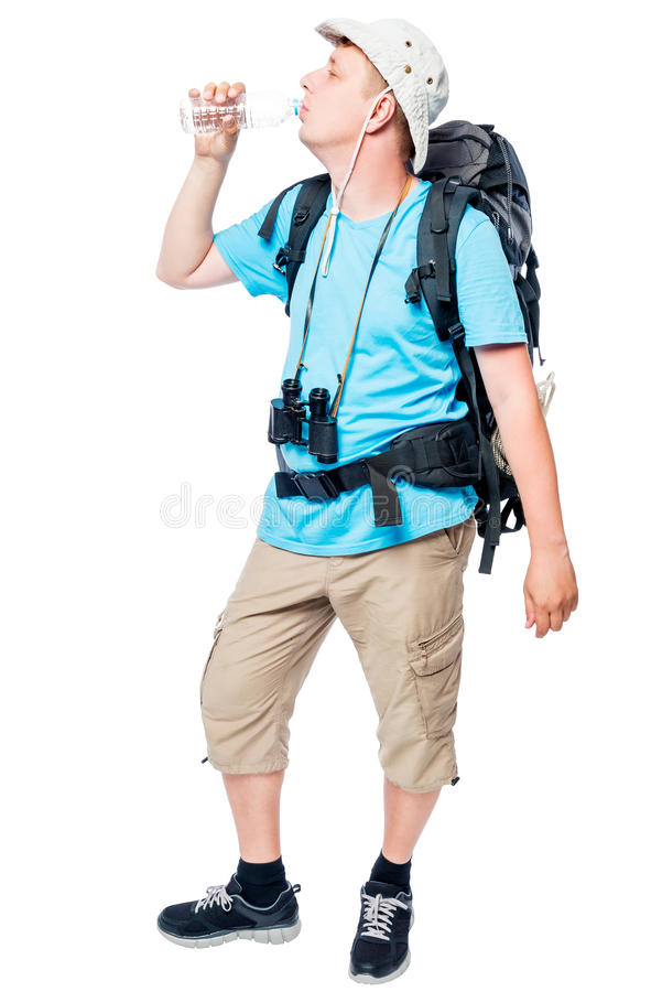 Hiker with a backpack eagerly drinks water from a bottle. On a white background stock photography