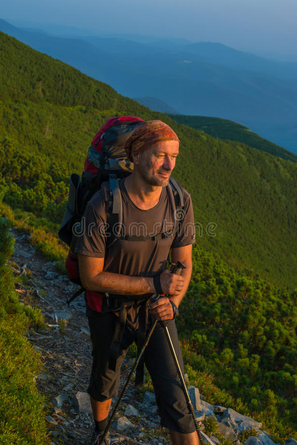 Hiker with backpack is resting and looks at the rising sun in mo. Untains. Man in thought on the background of the sky and mountains in the morning haze. Sunrise royalty free stock photos
