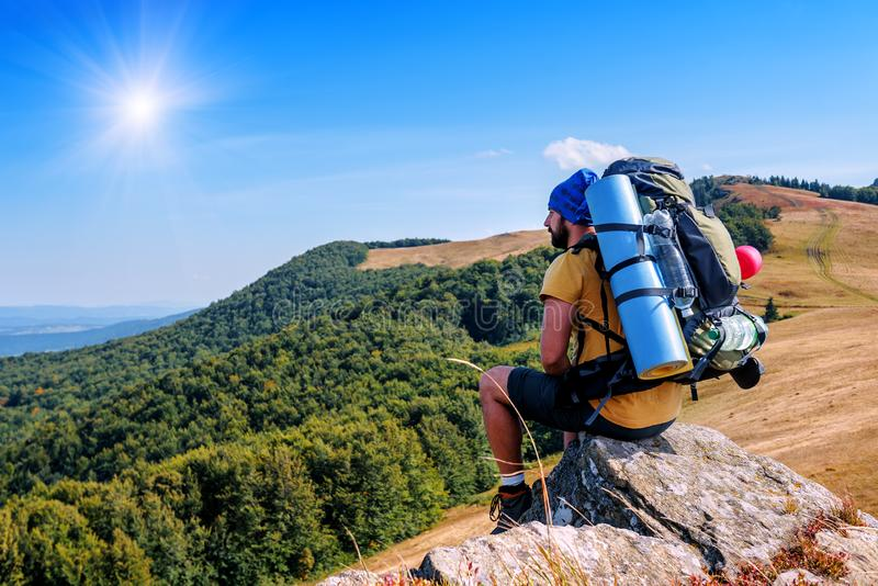 Hiker, tourist with backpack is resting on the rock royalty free stock image