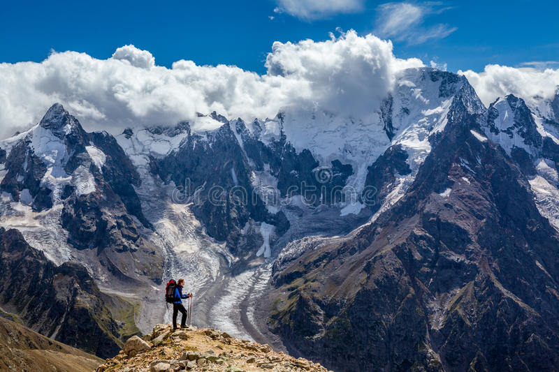 Hiker with backpack standing on mountain top and enjoying scene stock images