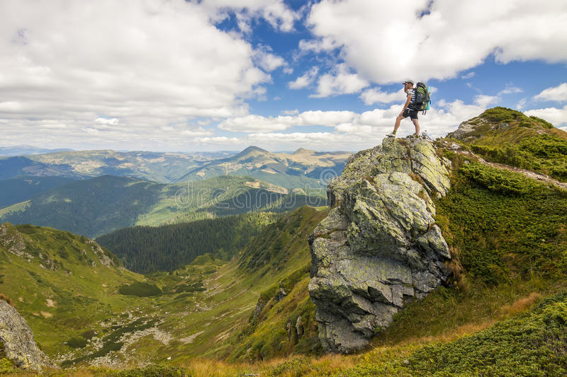 Hiker with a backpack standing o big stone in green rocky mounta stock images