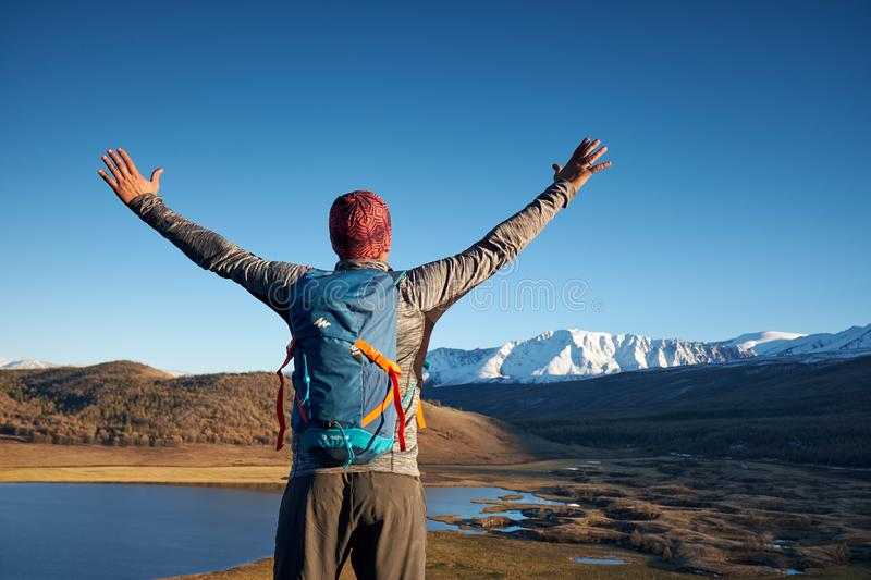 Hiker with backpack standing on top of a mountain with raised hands royalty free stock photography