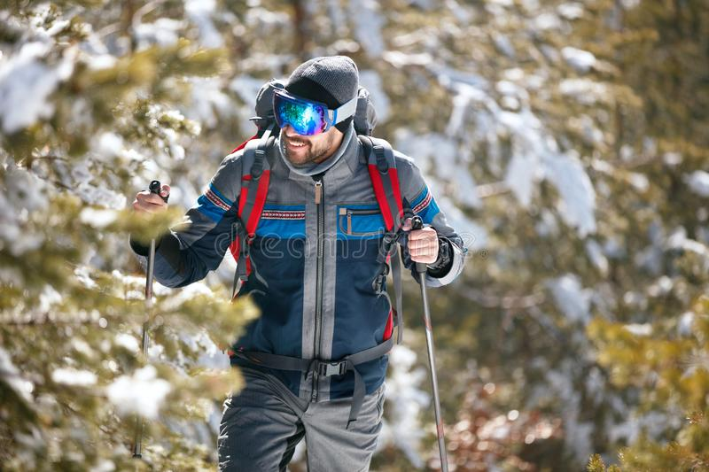 Hiker with backpack trekking in mountains. Cold weather, snow on. Smiling hiker with backpack trekking in mountains. Cold weather, snow on hills. Winter hiking royalty free stock photo