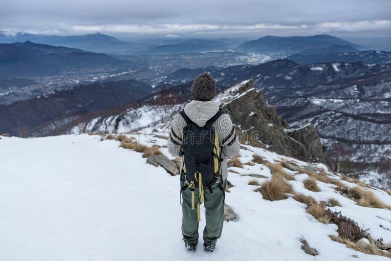 Hiker backpacker женщины смотря взгляд высокий вверх на Альпах Вид сзади, снег зимы холодный, темные облака и overcast стоковая фотография