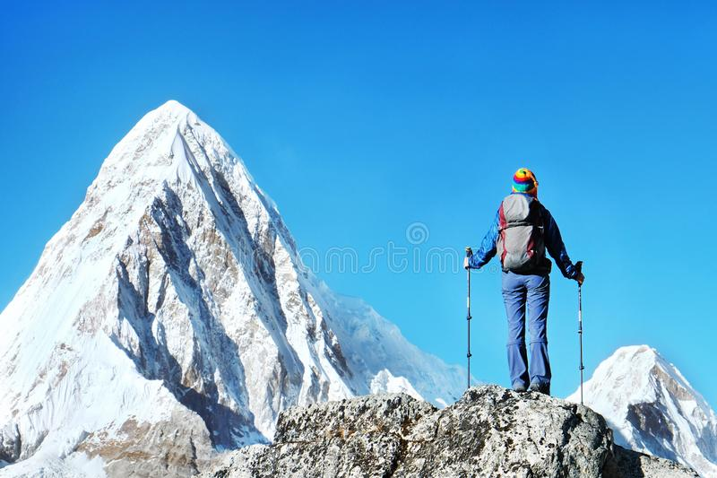 Hiker with backpacks reaches the summit of mountain peak. Success freedom and happiness achievement in mountains. Active sport royalty free stock photography