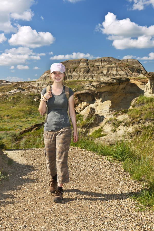 Hiker in badlands of Alberta, Canada. Smiling girl walking on path at the Badlands in Dinosaur provincial park, Alberta, Canada stock photos