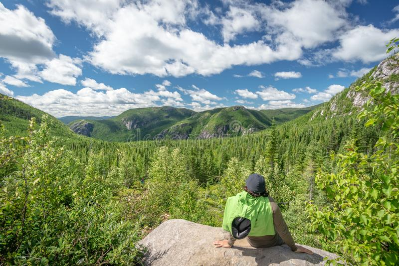 Hiker and beautiful view in Les Grands-Jardins National Park, Quebec. Single hiker man resting and looking at a beautiful mountain view in Les Grands-Jardins stock photo