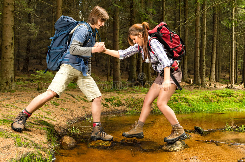 Hiker boy help trekking girl crossing creek royalty free stock images