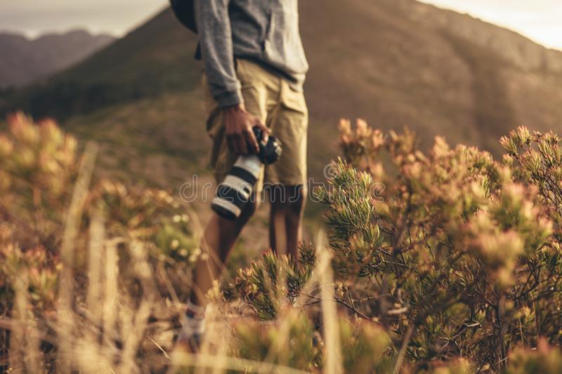 Hiker with camera. Mid section shot of man standing on mountain trail with his dslr camera. Focus on wild plants on mountain trail with a photographer standing royalty free stock photos