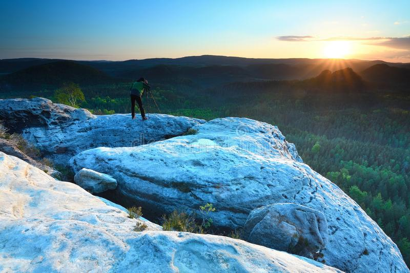 Hiker with camera on tripod takes picture from rocky summit. Alone photographer at edge photograph misty landscape colorful forest in valley stock photography