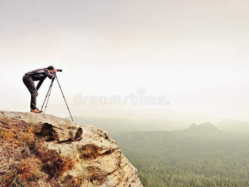 Hiker with camera on tripod takes picture from rocky summit. Alone photographer on summit. Hiker with camera on tripod takes picture from rocky summit. Alone royalty free stock photo