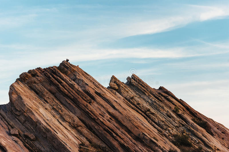 Hiker climbing on rock formations at Vasquez Rocks Natural Area Park. A hiker clambers on a giant rock shark fin-like formation at the popular park near Santa royalty free stock photo