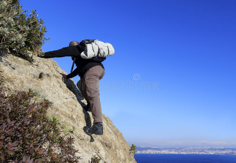 Hiker climbs on mountain stock photos