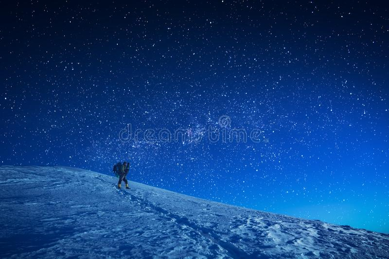 A hiker climbs up a snowy slope at night stock photo
