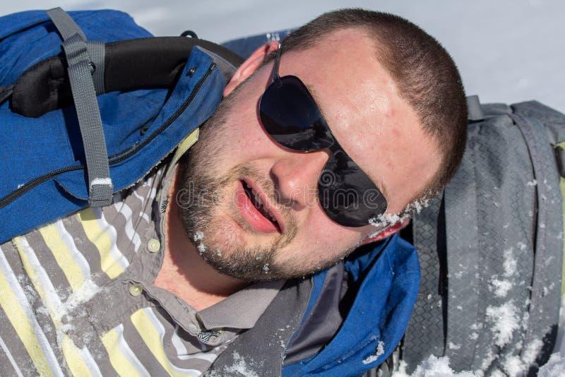 Hiker con gafas de sol con mochila puesta con nieve en la cara en invierno foto de archivo