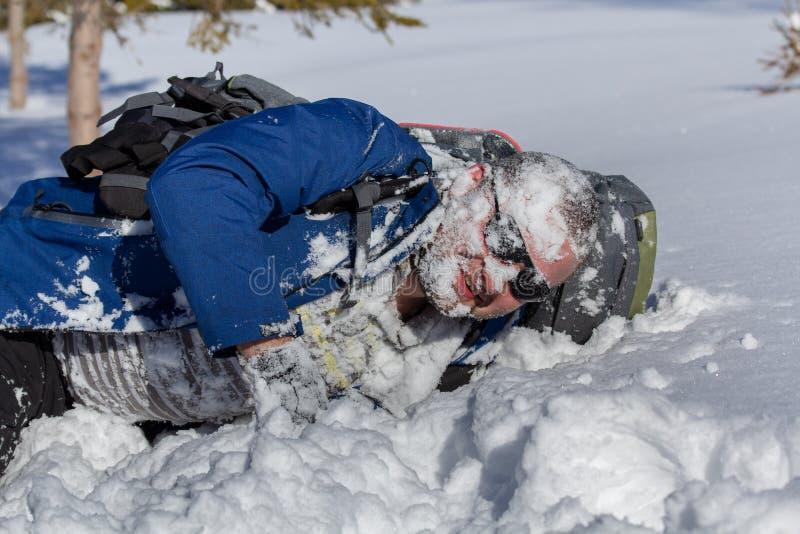 Hiker con gafas de sol con mochila puesta con nieve en la cara en invierno fotografía de archivo