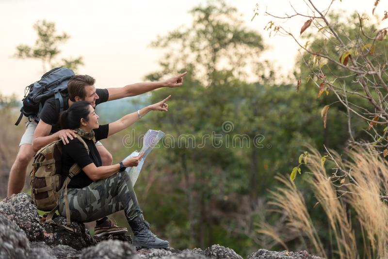 Hiker couple backpack pointing and sitting happy feeling freedom good and strong weight victorious facing on the natural mountain. Traveler going camping stock photos