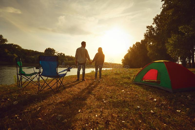 A hiker couple holding hands next to a tent by the lake at sunset. royalty free stock image