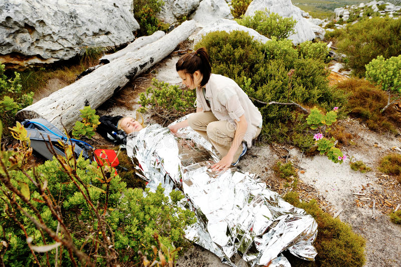 Hiker covered with emergency blanket stock photography