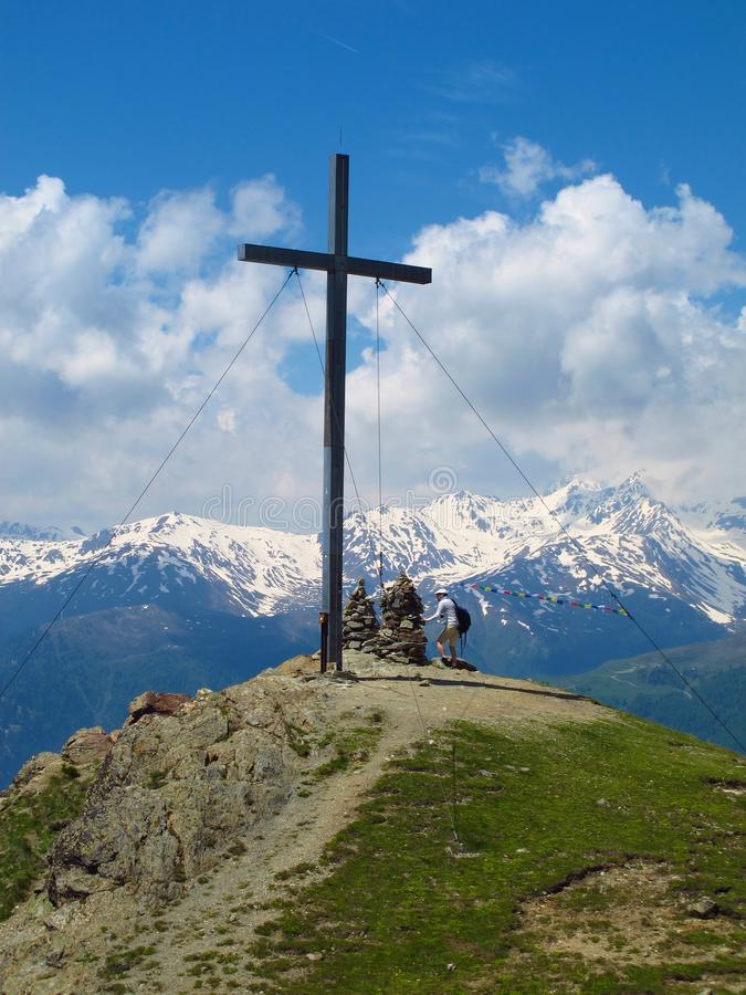 Hiker at cross atop Alpine mountain peak. South Tyrol, Italy - June 17, 2013: A lone hiker approaches a cross that marks the summit of the Spitzige Lun, an royalty free stock image