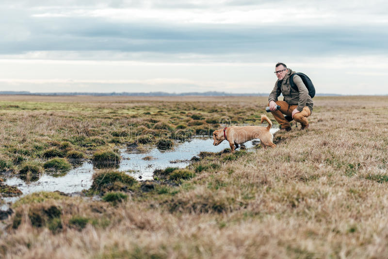 Hiker and dog by the pond. Hiker and dog standing by the pond in grassland on a cloudy day stock photography