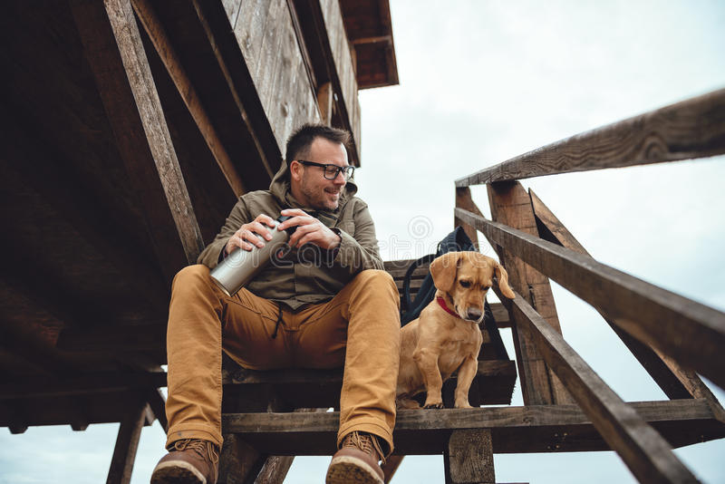 Hiker and dog resting. Hiker and dog sitting on the stairs of hikers rest cabin royalty free stock image