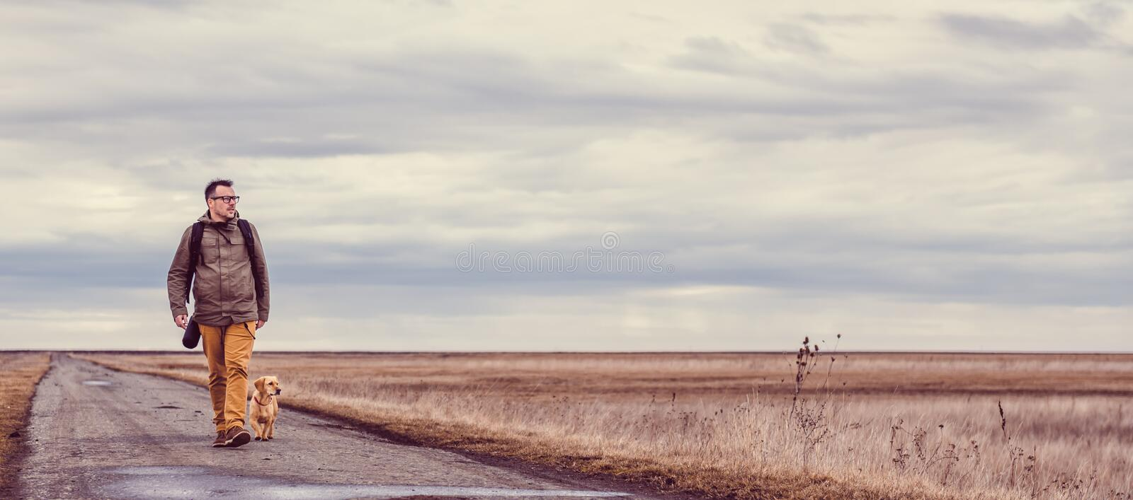 Hiker and dog walking on the road. Hiker and dog walking down a road on a cloudy day stock photography