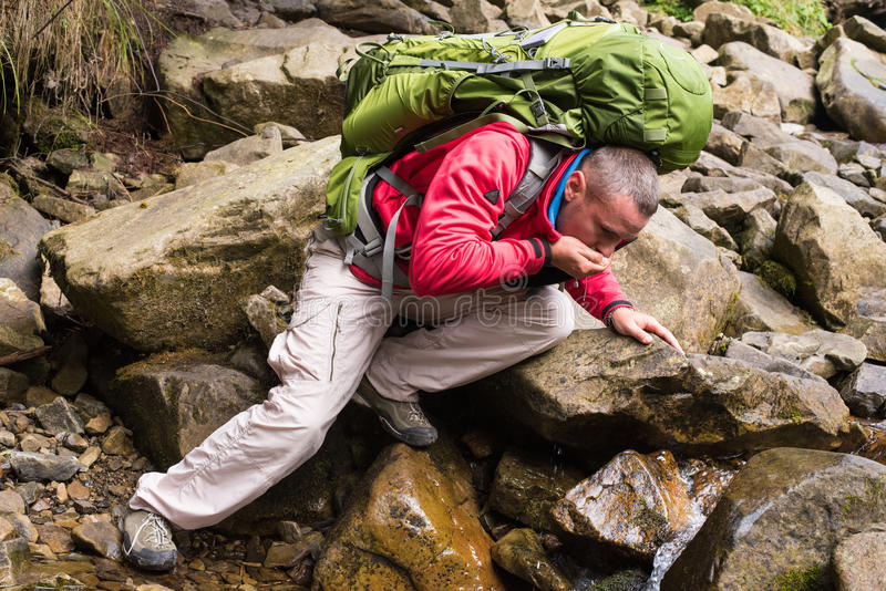 Hiker drinking stream water stock images