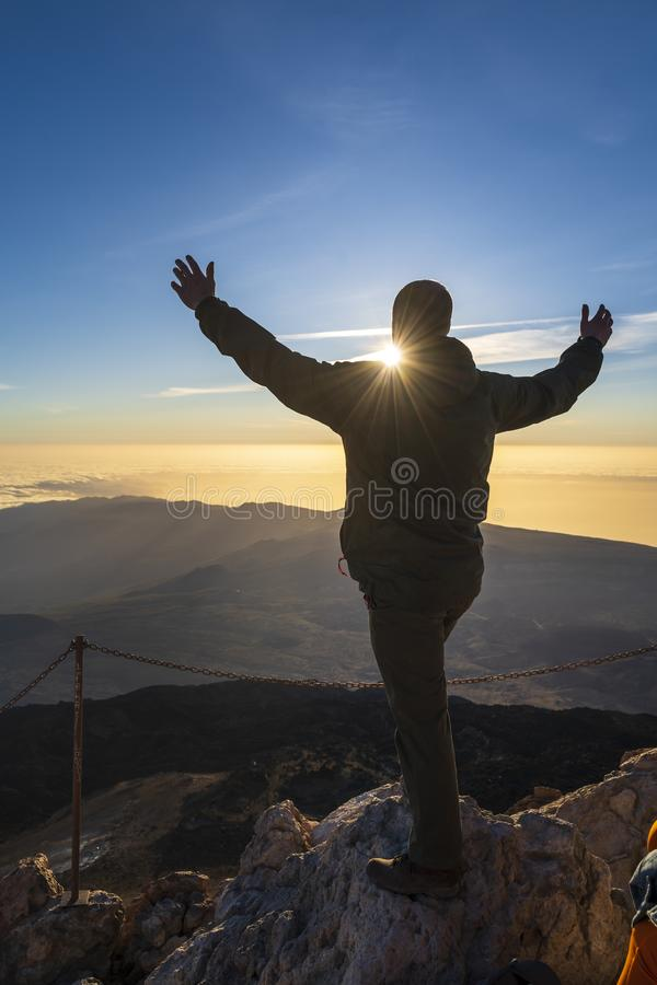 Hiker enjoying sunrise from top of the El Teide volcano royalty free stock image