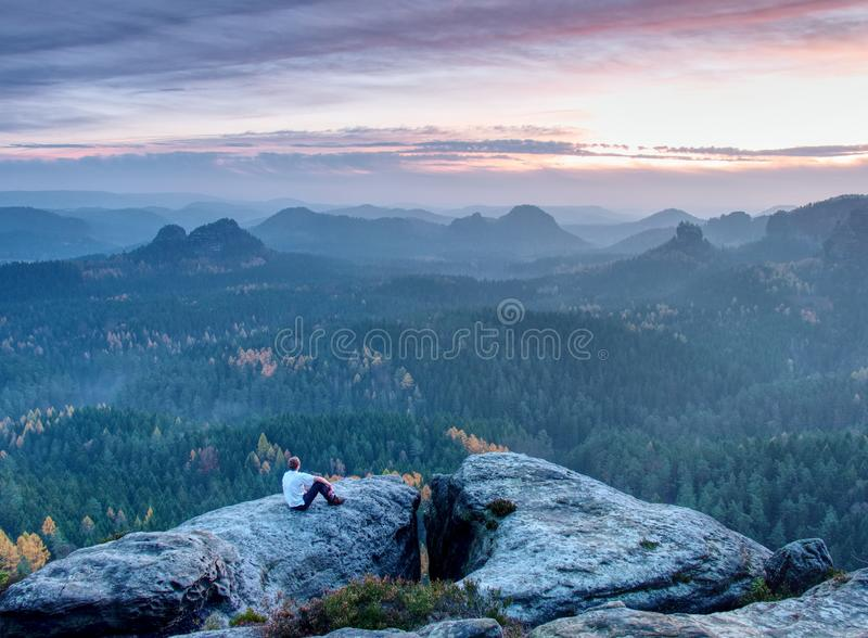 Hiker enjoying sunrise view in hilly landscape. Male hiker sitting and relaxing at the rocky summit of sharp mountain. Hiker is enjoying sunrise view in hilly royalty free stock photo