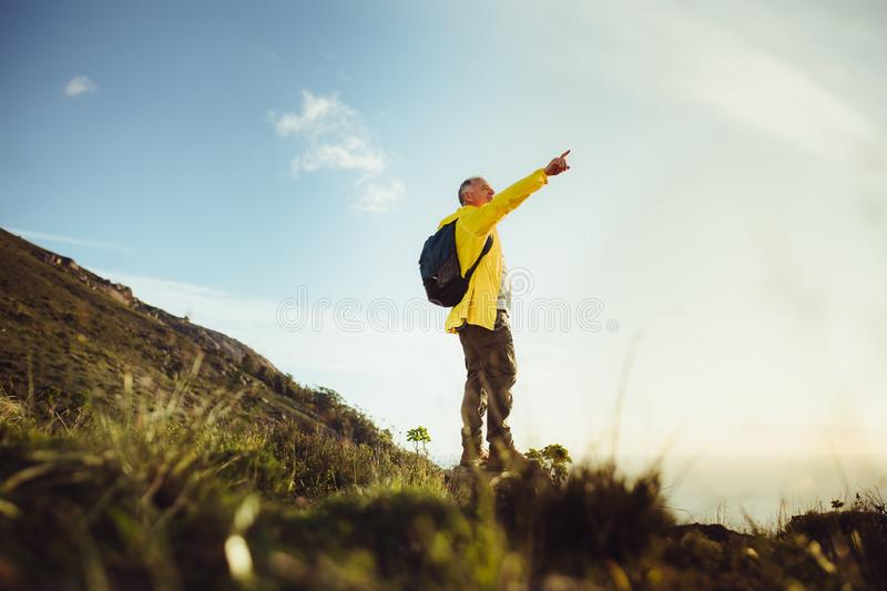 Hiker enjoying the view standing on a hill stock image