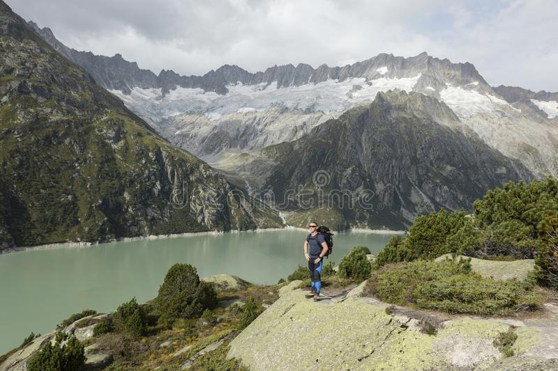Hiker enjoys the breathtaking view of a mountain lake royalty free stock photos