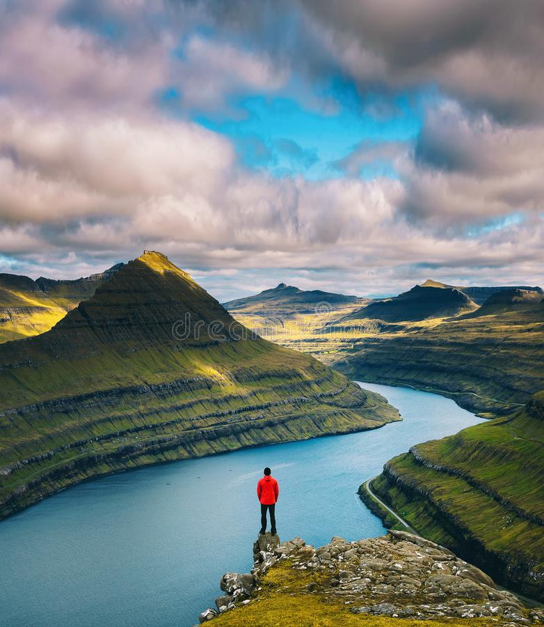 Hiker enjoys views over fjords from a mountain near Funningur on Faroe Islands. Hiker enjoys spectacular views over fjords from the summit of a mountain near royalty free stock photo