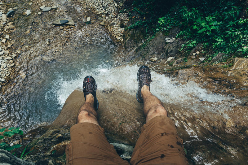 Hiker Explorer Sitting On Cliff With Waterfall View. Travel Lifestyle Adventure Vacations Concept royalty free stock image
