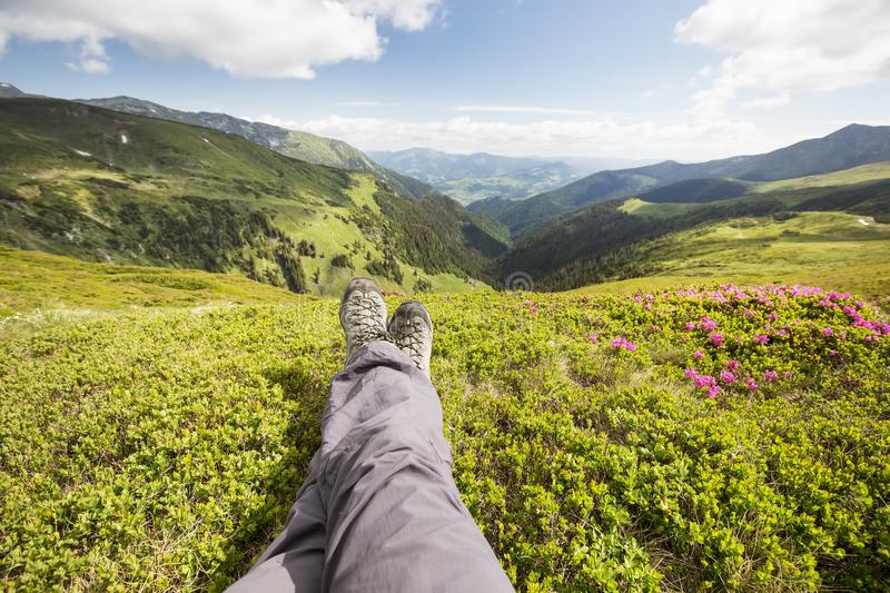 Hiker feet resting on top of the hill. Mountain hiking. Hiker feet resting on top of the hill. Beautiful nature landscape view with Rhododendron flowers royalty free stock photos