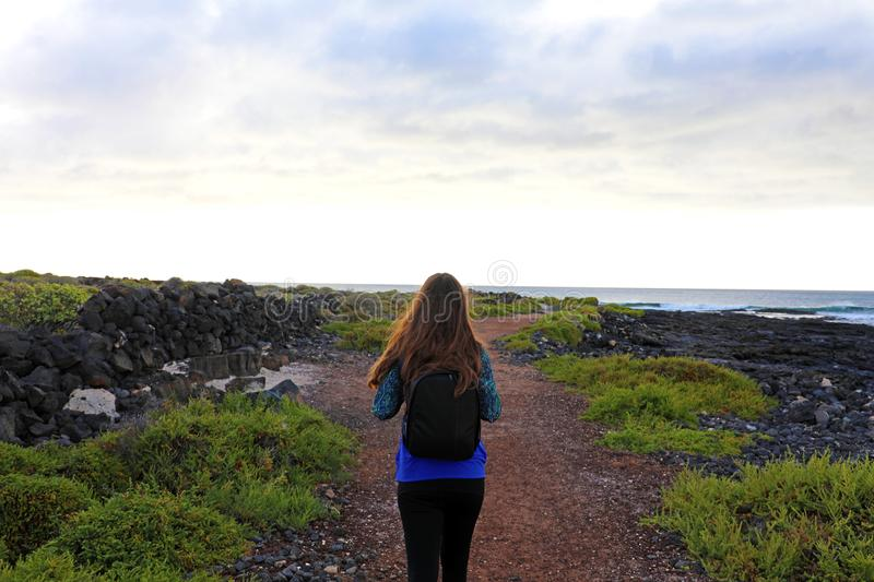 Hiker female walking in Lanzarote. Back view of young woman hiki stock images