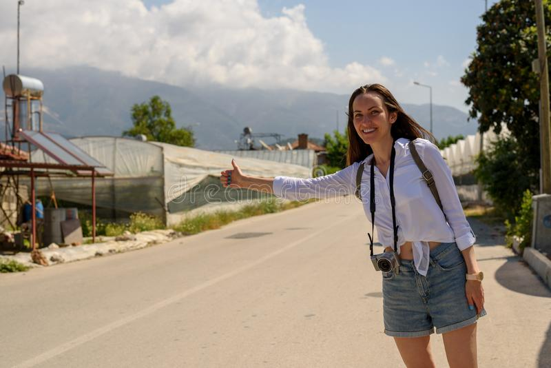 Hiker girl on the roadside catches car, hitchhiking, adventure, independent travel stock photos
