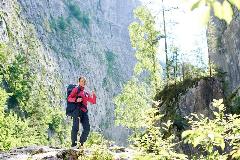 Hiker girl standing near enormous cliff wall. royalty free stock photography