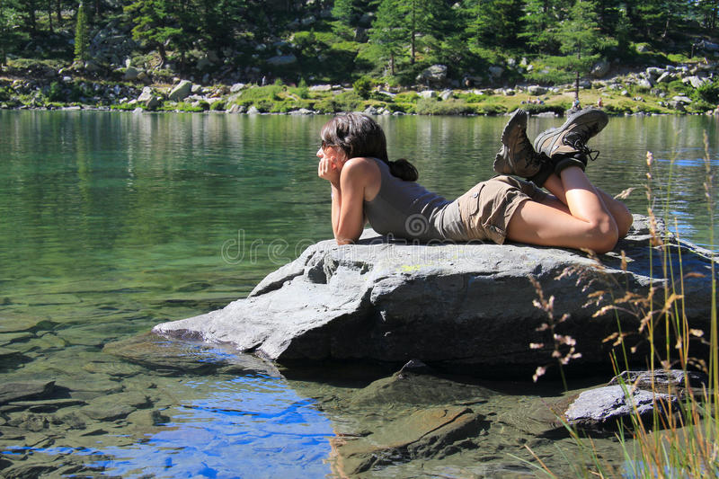 Hiker girl on a stone staring at lake stock photos