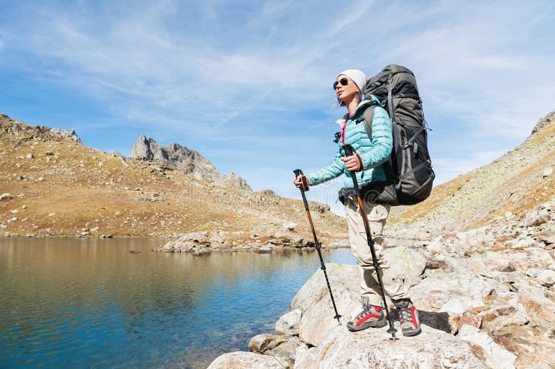 A hiker girl in sunglasses and a hat with a backpack and mountain gear with tracking treks in her hands looks at the stock photography