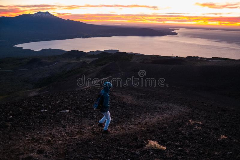 Woman hiker. Hiker goes down on the mountain trail with loose rocky ground and spectacular sunset view with lake and snow caped mountain. Chile royalty free stock photography