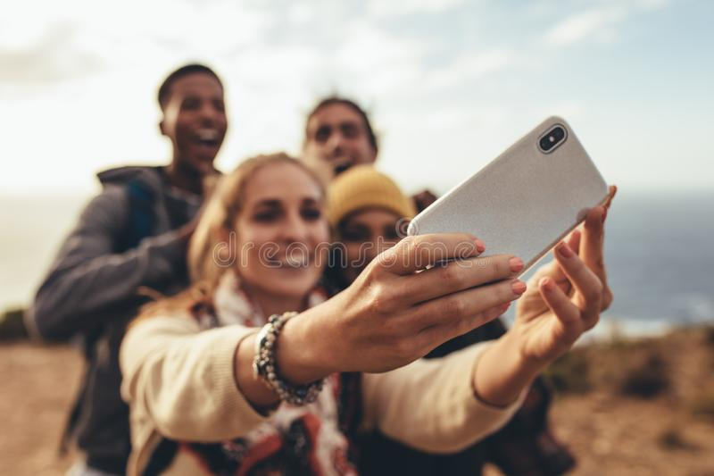 Hiker group selfie. Woman taking selfie with friends on hiking trip. Focus on female hands holding a smart phone and taking selfie with friends outdoors stock photo