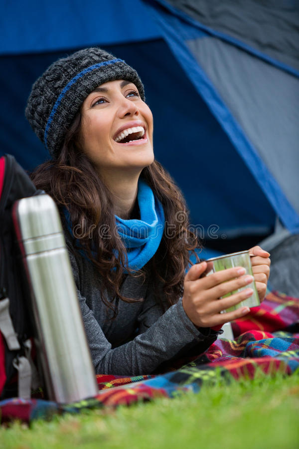 Hiker having a cup of coffee in tent royalty free stock photography