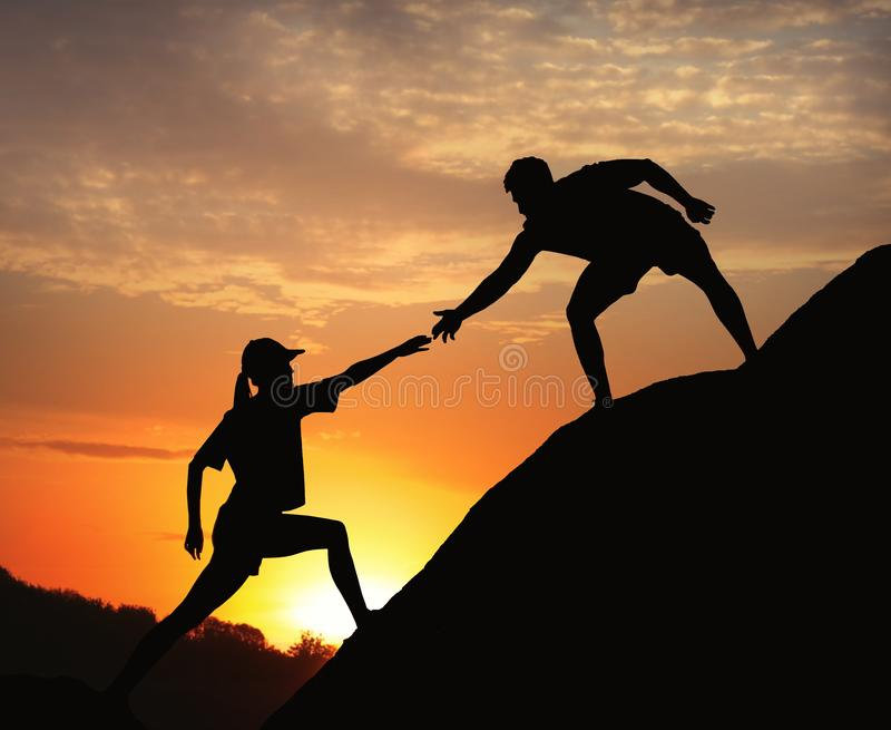 Hiker helping friend outdoors. Help and support concept. Hiker helping friend outdoors at sunset. Help and support concept royalty free stock images