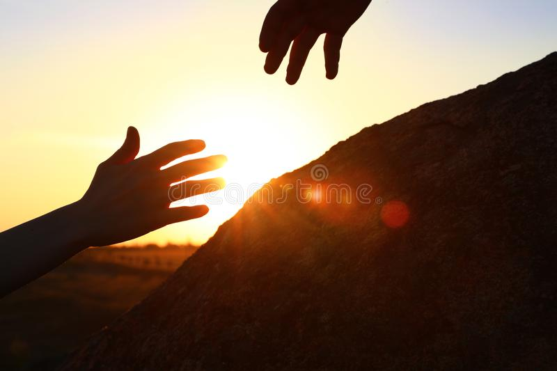 Hiker helping friend outdoors. Help and support concept. Hiker helping friend outdoors at sunset. Help and support concept stock photos
