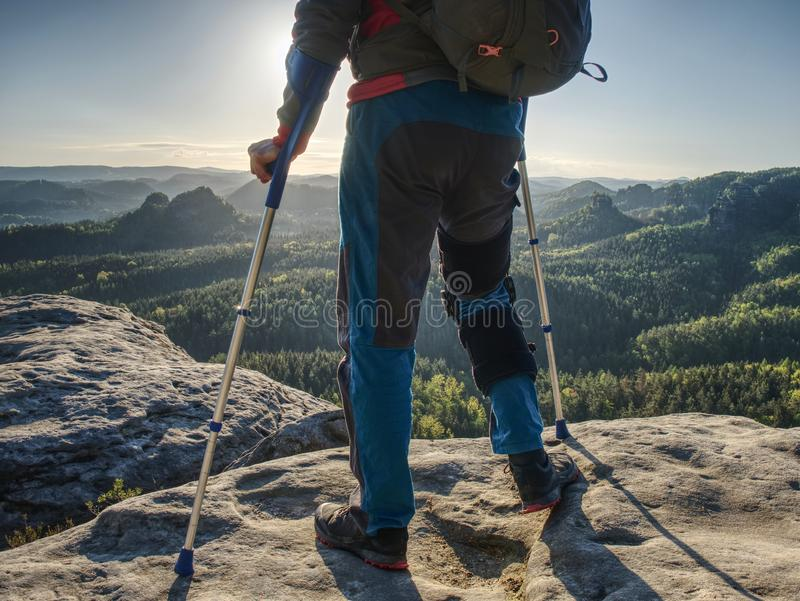 Hiker hold medicine stick,  injured knee fixed in knee feature royalty free stock photo