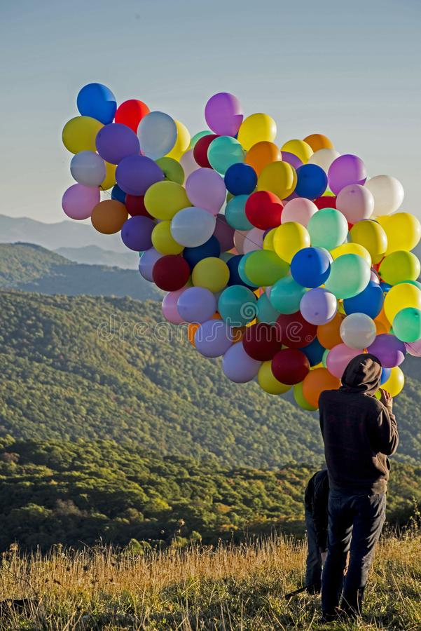 A hiker holds a cluster of colorful balloons on top of a mountains. royalty free stock photo
